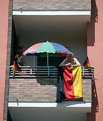 Man on balcony with German flag and parasol during football World Cup 2010 in Berlin Germany