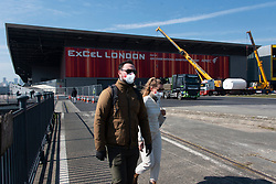 © Licensed to London News Pictures. 26/03/2020. London, UK. A couple wearing face masks walk past construction workers converting the ExCel Center into a 4,000 bed temporary hospital to deal with Coronavirus patients in London, United Kingdom on March 26, 2020.  The facility is to be called the NHS Nightingale. Photo credit: London News Pictures