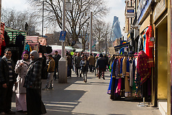 © Licensed to London News Pictures. 26/03/2015. London, UK. View of shops and shoppers along Whitechapel Road in east London on 23rd March 2015, with the Gerkin and City of London in the background. Whitechapel was today named as having the most unhealthy high street in London in a report by the Royal Society for Public Health. Image date 23rd March 2015. Photo credit : Vickie Flores/LNP