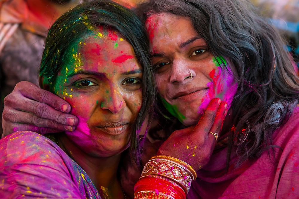 Women smearing colored powders on each other's faces, Lathmar Holi, Holi The Festival of Colors, Barsana, near Mathura, Uttar Pradesh, India.