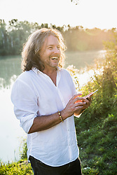 Man laughing while using digital tablet at river bank, Bavaria, Germany