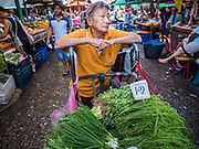 "12 JUNE 2015 - BANGKOK, THAILAND: A man selling herbs waits for customers in Khlong Toey Market in Bangkok. Khlong Toey (also called Khlong Toei) Market is one of the largest ""wet markets"" in Thailand. The market is located in the midst of one of Bangkok's largest slum areas and close to the city's original deep water port. Thousands of people live in the neighboring slum area. Thousands more shop in the sprawling market for fresh fruits and vegetables as well meat, fish and poultry.          PHOTO BY JACK KURTZ"