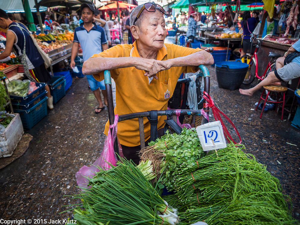 """12 JUNE 2015 - BANGKOK, THAILAND: A man selling herbs waits for customers in Khlong Toey Market in Bangkok. Khlong Toey (also called Khlong Toei) Market is one of the largest """"wet markets"""" in Thailand. The market is located in the midst of one of Bangkok's largest slum areas and close to the city's original deep water port. Thousands of people live in the neighboring slum area. Thousands more shop in the sprawling market for fresh fruits and vegetables as well meat, fish and poultry.          PHOTO BY JACK KURTZ"""