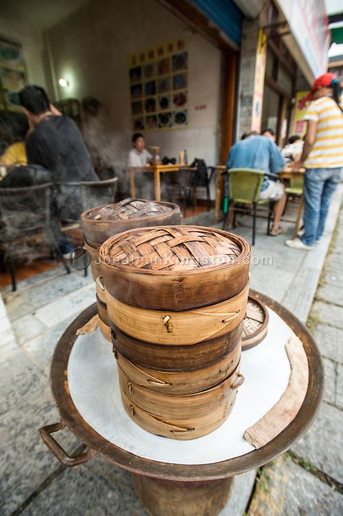 Bamboo steaming baskets full of freshly made food in front of a restaurant in Yangshuo, China.