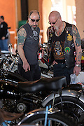 Leather clad bikers inspect classic motorbikes during the 74th Annual Daytona Bike Week March 8, 2015 in Daytona Beach, Florida. More than 500,000 bikers and spectators gather for the week long event, the largest motorcycle rally in America.