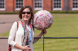 © Licensed to London News Pictures. 03/05/2015. London, UK. A tourist from Alabama, USA poses with a balloon tied to a railing outside the Golden Gates at Kensington Palace for the new daughter of the Duke and Duchess of Cambridge who was born the previous day. Photo credit : Stephen Chung/LNP