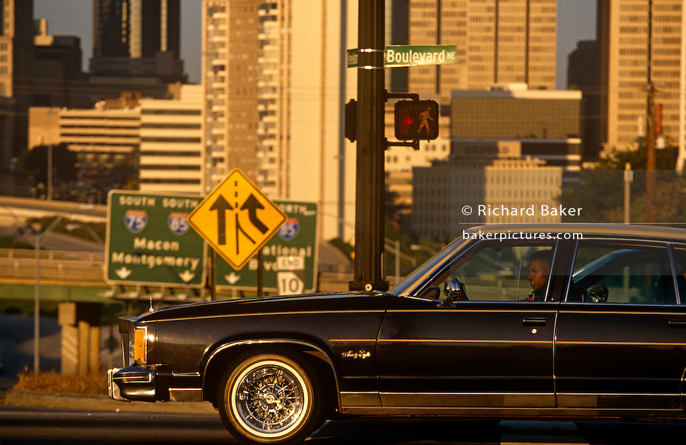 A driver in his gas-guzzling car and in the background, the skyline of downtown Atlanta.