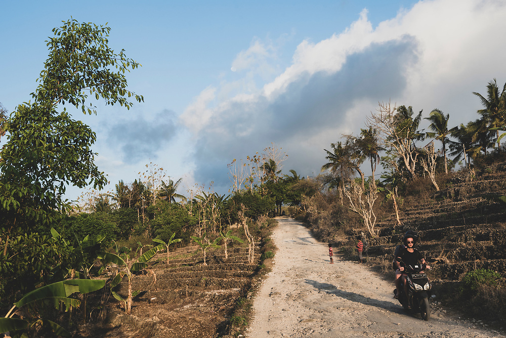 Nusa Penida, Bali, Indonesia - October 3, 2017: Two tourists ride a motorbike on the infamouly bumpy road toward Angel's Billabong on the island of Nusa Penida. Accidents are not uncommon.
