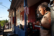 BETHLEHEM, PA – JUNE 2, 2011: A young Puerto Rican woman checks text messages from her friend on State Street in Southside Bethlehem.<br /> <br /> As the population of second and third generation Hispanics increases dramatically in the United States, a new boldness can be sensed among Latinos in America, stretching far beyond the southern border states. Demographers in Pennsylvania say the towns of Bethlehem, Allentown and Reading are set to become majority-minority cities, where Hispanics comprise a bigger portion of the population than whites. As this minority population increases dramatically in the region, Latinos are inching closer to their own realization of the American Dream, while gradually shifting the physical and cultural landscapes of their communities.