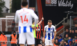 Brighton & Hove Albion's Dale Stephens (right)is shown a yellow card by referee Michael Oliver (hidden) during the Emirates FA Cup, third round match at the Vitality Stadium, Bournemouth.