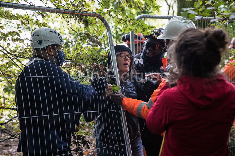 National Eviction Team bailiffs working on behalf of HS2 Ltd push an anti-HS2 activist through a fence during evictions from a wildlife protection camp in the ancient woodland which inspired Roald Dahl's Fantastic Mr Fox at Jones' Hill Wood on 1 October 2020 in Aylesbury Vale, United Kingdom. Around 40 environmental activists and local residents, some of whom living in makeshift tree houses 60 feet above the ground, were present during the evictions at Jones' Hill Wood which had served as one of several protest camps set up along the route of the £106bn HS2 high-speed rail link in order to resist the controversial infrastructure project.