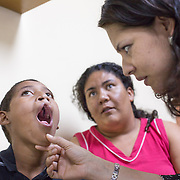 CAPTION: The doctors at Hospital Escuela recently operated on 12-year-old Santos Medina's cleft palate. For this, he had to travel to Tegucigalpa for nine hours from his home in a mountainous region called Yoro. Unfortunately, it seems that Santos' mother does not really care about his problem, so it's his neighbours who have been helping him. Owing to the complexity of the case, a social worker has been mediating. According to the neighbours, if Santos goes back to his mother, he will never get access to surgery again. Following careful investigation, the social worker will need to make a recommendation to a legal counsellor. Sadly, this is a long process with many follow-ups to be done. During this time, there is a significant probability that Santos' mother will try to forcefully retrieve him. However, the doctors remain hopeful that it will be possible to restrain her until he's had the medical attention and care he needs.   LOCATION: Hospital Escuela, Tegucigalpa, Honduras. INDIVIDUAL(S) PHOTOGRAPHED: From left to right: Santos Pablo Medina Hernandez, Rosmery Martinez and Dr Gloria Baleska Caderes Estrada.