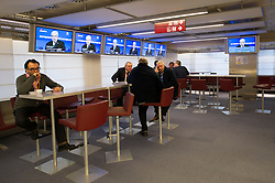 A few remaining journalists and council employees sit in the press bar as Dimitris Christofias, president of Cyprus, speaks during the EU Council presidential press conference, which is broadcast live on EbS, the European Commission Broadcast Service, following the conclusion of the EU Summit, at the European Council headquarters in Brussels, Belgium on Friday, Dec. 14, 2012. (Photo © Jock Fistick)