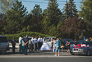 A wedding party stands outside cars across the street from the Memorial of Glory in Tiraspol, Transnistria.