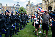 Riot police form a barrier between media and supporters of Tommy Robinson real mame Stephen Yaxley - Lennon as they protest outside the Houses of Parliament after he was sentenced  to nine months in prison for contempt of court. He was found guilty of filming defendants accused of child sex offences outside Leeds Crown Court and live-streaming the footage on Facebook Live in May, 2018.