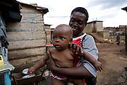 A mother and baby boy on the outskirts of Kalerwe market, Kampala, Uganda.