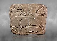 Hittite monumental relief sculpted orthostat stone panel. Limestone, Karkamıs, (Kargamıs), Carchemish (Karkemish), 900-700 B.C. Hunting carriage.  Anatolian Civilisations Museum, Ankara, Turkey.<br /> <br /> Two human figures; one handling the carriage, the other throwing arrows. Both figures are wearing a headdress shaped like a skullcap. The dagger at the waist of the figure throwing arrow draws attention. There is an animal between the legs of the horse having an aigrette over its head. <br /> <br /> Against a grey art background. .<br />  <br /> If you prefer to buy from our ALAMY STOCK LIBRARY page at https://www.alamy.com/portfolio/paul-williams-funkystock/hittite-art-antiquities.html  - Type  Karkamıs in LOWER SEARCH WITHIN GALLERY box. Refine search by adding background colour, place, museum etc.<br /> <br /> Visit our HITTITE PHOTO COLLECTIONS for more photos to download or buy as wall art prints https://funkystock.photoshelter.com/gallery-collection/The-Hittites-Art-Artefacts-Antiquities-Historic-Sites-Pictures-Images-of/C0000NUBSMhSc3Oo