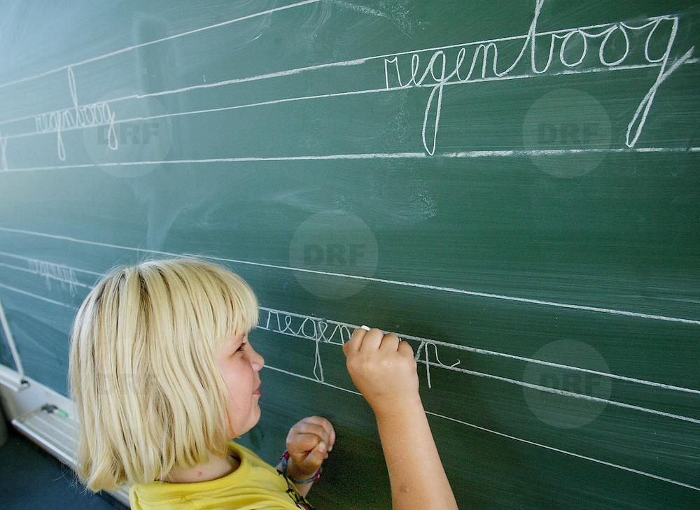 Nederland Rotterdam 2 mei 2005 .Meisje leert schrijven op schoolbord. Leerling oefent op schoolbord..Foto David Rozing