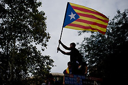 October 3, 2017 - Barcelona, Catalonia, Spain - A man waves a estelada or pro-independence flag during a protest against Spanish police brutality in Barcelona. A general strike goes over Catalan territory to protest against brutality by police during a referendum on the region's secession from Spain that left near nine  hundred of people injured. (Credit Image: © Jordi Boixareu via ZUMA Wire)