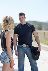 cowboy looking at a girl outdoors on a rural road