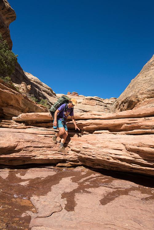 Backpacker hiking down a canyon in Cedar Mesa, Utah.