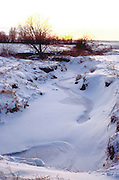 Sunset on a frozen creek on the Iowa plains.  Garden City Iowa USA
