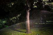 Sprinklers spray water against a tree on the University of Colorado campus in Boulder, Colorado.