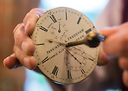 """© Licensed to London News Pictures. 23/10/2014. Guildford, UK. Michael Tooke changes the time on a marine chronometer mechanism from the 1860's made by Parkinson and Frodsham. As British Summer Time comes to an end, staff at Horological Workshops start the task of changing the 100's of clocks at their store in Guildford, Surrey, UK. Michael Tooke who has owned the store for over 40 years and worked in the clock business all his life said. """"at this time of year we get a lot of people who bring clocks in for repair after they have changed the time incorrectly by winding back the hands manually"""". Clocks change on Sunday morning 26th October. Photo credit : Stephen Simpson/LNP"""