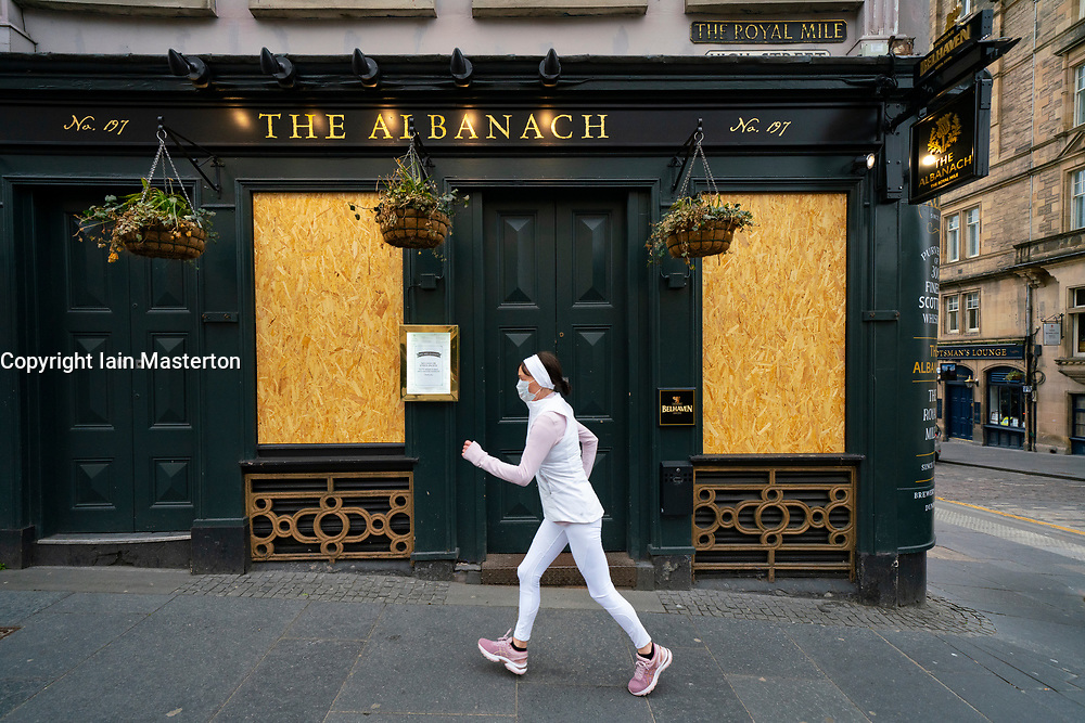 Edinburgh, Scotland, UK. 29 April 2020. Views of Edinburgh Old Town as coronavirus lockdown continues in Scotland. Streets remain deserted and shops and restaurants closed and many boarded up. Scottish Government now recommends public to wear face masks. Female jogger wearing face mask runs past a closed and boarded up Albanach pub on the Royal Mile. Iain Masterton/Alamy Live News
