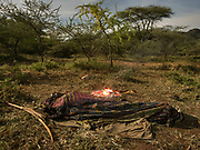 After a day hunt, a man sleep out in the open. At the Hadza camp of Dedauko.