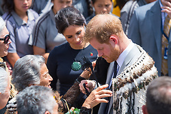 The Duke of Sussex takes off a traditional Maori cloak called a Korowai as the Duchess of Sussex looks on during a visit to Te Papaiouru, Ohinemutu, in Rotorua, before a lunch in honour of Harry and Meghan, on day four of the royal couple's tour of New Zealand.