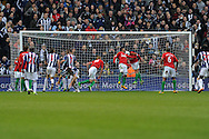 WBA score their 2nd goal, an own goal as Swansea city's Jonathan De Guzman (20 in red) nods the ball back into his own net after Angel Rangel (no22) had initially cleared.  Barclays Premier league, West Bromwich Albion v Swansea city at the Hawthorns stadium in West Bromwich, England on Saturday 9th March 2013.  pic by  Andrew Orchard, Andrew Orchard sports photography,