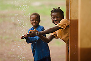 Children wash their hands with water dripping from the roof during a downpour at the Nyologu Primary School in the village of Nyologu, northern Ghana, on Wednesday June 6, 2007.
