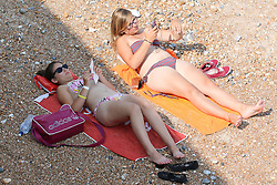© Licensed to London News Pictures. 23/07/2014. Brighton, UK. People relaxing and sunbathing on Brighton beach. The weather is expected to be one of the hottest days of the year with temperatures to  reach around the 28C in Brighton and the South Coast. Photo credit : Hugo Michiels/LNP