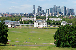 © Licensed to London News Pictures 08/06/2021. Greenwich, UK. A view of Canary Wharf from Greenwich Park, London as people enjoy the hot sunny weather today. Photo credit:Grant Falvey/LNP