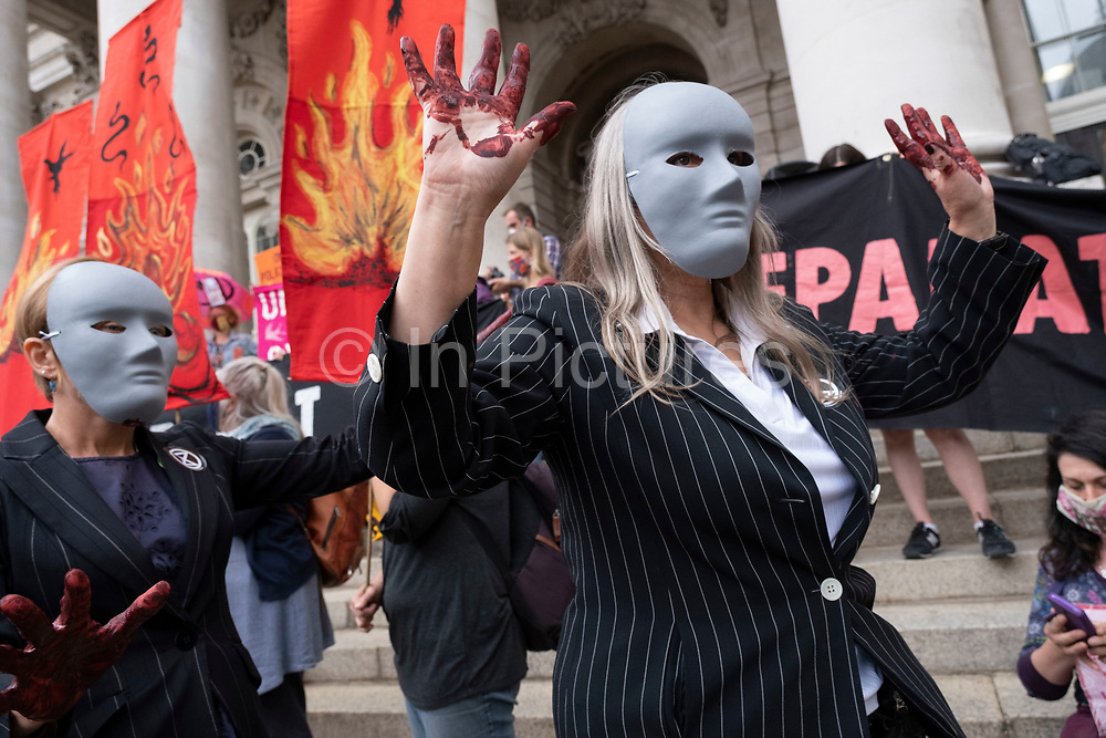 Bankers with blood on their hands at the  Walk of Shame disruptive mach through the City of London by environmental group Extinction Rebellion on 4th September 2020 in London, United Kingdom. The walk visited various locations in the financial district, to protest against companies and institutions with historical links to the slave trade, or who finance or insure projects which are seen as ecologically unsound. The message by the group is that 'apologies and token attempts at diversity are not enough to address this legacy and present reality. Our demand is reparations and reparatory justice for those affected by colonial and neo-colonial exploitation'. Extinction Rebellion is a climate change group started in 2018 and has gained a huge following of people committed to peaceful protests. These protests are highlighting that the government is not doing enough to avoid catastrophic climate change and to demand the government take radical action to save the planet.