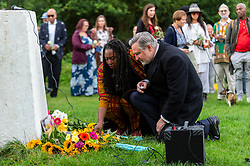 © Licensed to London News Pictures. 03/08/2021. LONDON, UK. Dawn Butler MP for Brent Central, (C), lays floral tributes at a vigil at Barn Hill Pond, Fryent Country Park near Wembley to remember the lives of sisters Bibaa Henry and Nicole Smallman, on what would have been Nicole's 29th birthday.  The sisters were murdered in the park in June 2020 whilst celebrating Bibbaa's birthday.  Reclaim These Streets have worked with former Archdeacon of Southend, the Ven. Wilhelmina (Mina) Smallman, the late sisters' mother, to organise the vigil and attendees were encouraged to wear green and purple, the sisters' favourite colours, or light a candle.  Photo credit: Stephen Chung/LNP
