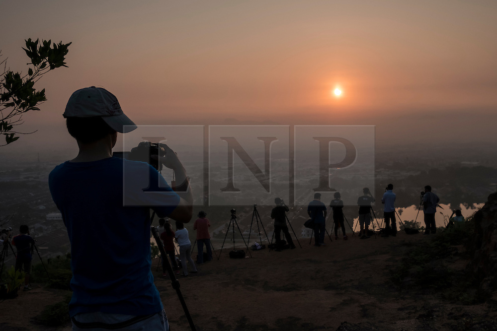 © Licensed to London News Pictures. 09/03/2016 Ipoh, Malaysia. Photographers gathered to take pictures of a partial solar eclipse over the city of Ipoh in Malaysia, Wednesday, March 9, 2016. Photo credit : Sang Tan/LNP