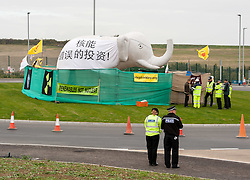 "© Licensed to London News Pictures. 19/10/2015. Hinkley Point, Somerset, UK.  Officials deliver papers to an Anti-nuclear protest by the group ""Osborne's Folly"" (after the Chancellor George Osborne), protesting against the proposed new nuclear power station Hinkley C and against Chinese investment in the project.  The papers ask the protesters to leave by 5pm or legal proceedings will begin to regain possession of the land. The group has occupied a roundabout near the site and erected an inflatable white elephant with a banner written in Chinese and say they want to send a message to the visiting Chinese President Xi Jinping that EDF's Hinkley C would be ""a bad investment"" for the Chinese state. They say that the stalled project has become ""Osborne's Energy Folly"" and should now be abandoned.  Theo Simon, one of the campaigners said: """"Ironically, the Chinese are leading the world in renewable energy investment in their own country, where there is also a growing anti-nuclear movement"". Photo credit : Simon Chapman/LNP"