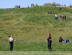 © Licensed to London News Pictures. 19/04/2020. London, UK. Two women exercise on a warm Spring day as Police patrol Primrose Hill enforcing lockdown rules on social distancing and exercise as Ministers urge councils to keep parks open to the public during lockdown. Photo credit: Alex Lentati/LNP