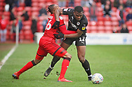 Walsall FC forward Morgan Ferrier (16) and Barnsley defender Dimitri Cavare (12) tussle for the ball during the EFL Sky Bet League 1 match between Walsall and Barnsley at the Banks's Stadium, Walsall, England on 23 March 2019.