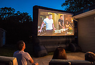 """Merrick, New York, USA. 11th June 2017.  At bottom left, CHRIS EDOM, """"American Grit"""" TV contestant, 48, of Merrick, hosts backyard Viewing Party for Season 2 premiere. The Fox network reality television series show projected on large screen, with (L-R) JOHN CENA, and 2 of his Cadre members, JOHN BURKE and RIKI LONG. Edom was last contestant picked for a team that episode."""
