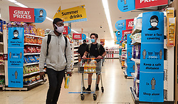 © Licensed to London News Pictures. 12/07/2021. London, UK. Shoppers wearing face coverings walk past 'Wear a Face Covering' and 'Keep a safe distance' signs in a Sainsbury's supermarket in London. Prime Minister Boris Johnson will provide an update to step four of easing the Covid-19 lockdown in a press conference later today. It is expected that the face coverings in shops, pubs and mass events will no longer be mandatory after Freedom Day on 19 July. Businesses will be able to set rules for entry to their own premises. Vaccines Minister Nadhim Zahawi said that people will still be expected to wear a face covering in 'enclosed indoor spaces', though it will no longer be legal to do so. Photo credit: Dinendra Haria/LNP
