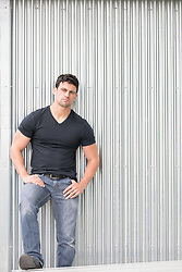All American man with green eyes against a wall
