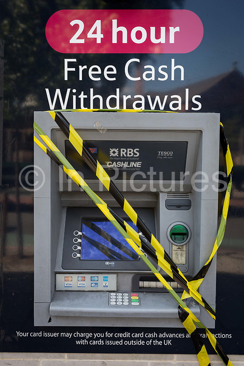 A 24hr ATM cash dispenser operated by the RBS banking group and the Tesco supermarket is taped up and out of order in Camberwell, on 5th July 2017, in London, England.