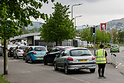 MERTHYR TYDFIL, WALES - 09 MAY 2020: KFC worker stops cars entering the driver through to KFC as its full.