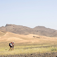 25 March 2007:  Participants walk across a blooming desert because of a rainy winter between Irhs and Khermou during the first stage of  the 22nd Marathon des Sables, a 6 days and 151 miles endurance race with food self sufficiency across the Sahara Desert in Morocco. Each participant must carry his, or her, own backpack containing food, sleeping gear and other material.