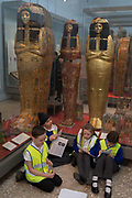 Schoolchildren work on projects beneath New Kingdom 1279-1213BC Egyptian Mummies of Henutmehyt in the British Museum, on 28th February 2017, in London, England.