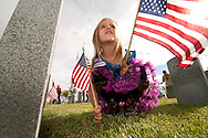 """Ellie Beasley, 6, a Daisy Girl Scout from Redding, places flags at the Northern California Veterans Cemetery in Igo.  About 50 youth from the Girl Scouts and Boy Scouts were central in placing flags. at the Cemetery in Igo on Friday, May 25, 2012.  Stephen Jorgensen, Assistant Deputy Secretary Veterans Memorial and Cemetery, said there was around 1,700 grave sites at the cemetery.  He was excited to address the youth, """"This is a wonderful opportunity to teach the scouts what Memorial Day is all about,"""" Jorgensen said."""