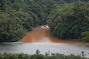 Brown sediment filled water from the gold mining areas meets the clear water from another river in the Amazon seen from the Interoceanic highway. This polluted water which often has a high mercury content from the extraction process is one of the larger environmental concerns in the area.